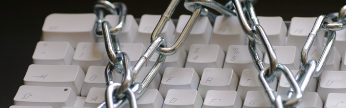Computer Keyboard with metal chains wrapped around it symbolizing writer's block